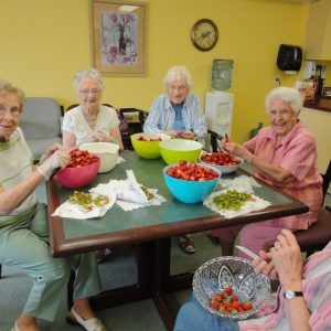 Seniors preparing strawberries